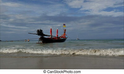 Thai traditional wooden boat with ribbon decoration at ocean...