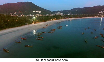 Many fishing boats are on moorage near beach at the evening....