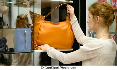 A beautiful girl picks a bag. bag shop Fashion store