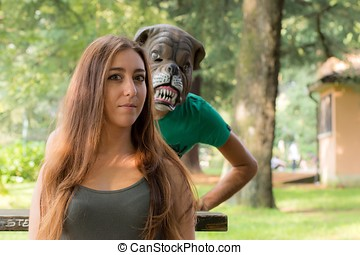 Girl and masked boy - Boy with a dog mask behind a beautiful...