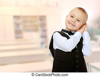 Trendy little boy in a black suit with a tie.