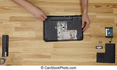Male engineer repairs laptop. Wooden table top view.