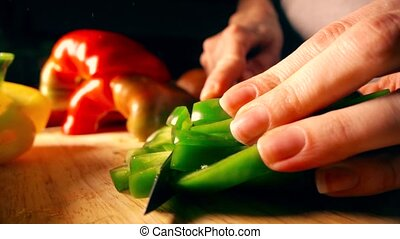 Amateur female cook cutting green sweet pepper. Healthy...
