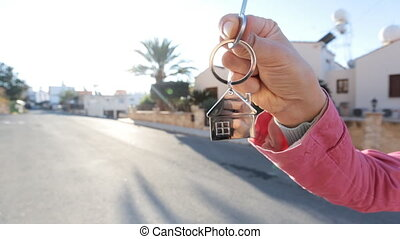 Hand holds the key to the house - Holding house keys on...