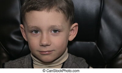 Serious boy in office on armchair, close-up - Boy in gray...