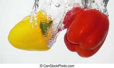 Two Ripe Peppers Falling Through Water. - Two Ripe, Colorful...