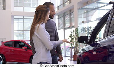 Couple chooses car at the dealership