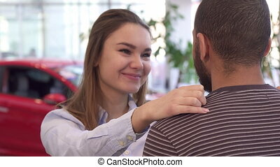 Girl hugs her boyfriend at the dealership - Pretty caucasian...