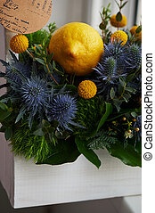 A spring bouquet in a white wooden box in the yellow-green...