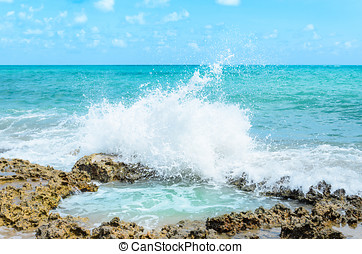 Ocean water splashing on rocks and forming a natural pool in...