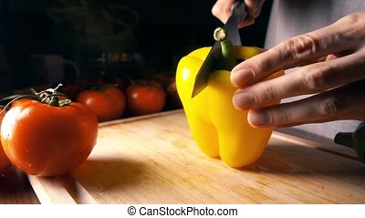 Female cook cutting whole yellow sweet pepper. Healthy...