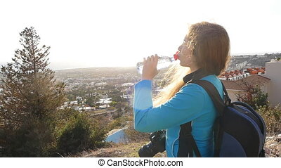 Woman tourist with backpack drinking water