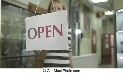 open sign is turned to closed in a storefront window. woman flipping nameplate with open sign