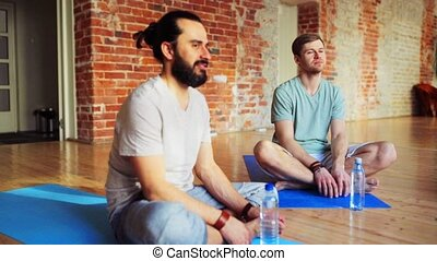 men with water resting on yoga mats in gym - fitness, sport...