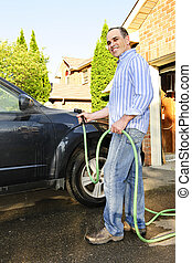 Man washing car on driveway - Man washing his car on the...