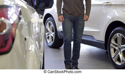 Man looks at the car wheel at the dealership - Handsome...