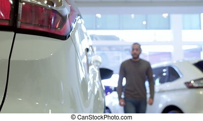 Man gets inside the crossover at the dealership - Attractive...