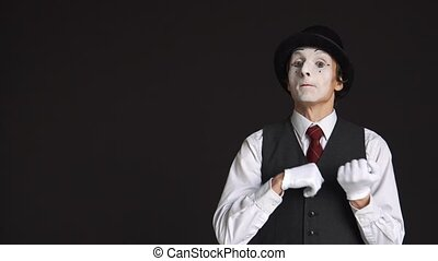 man MIME showing something on the black background.