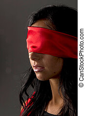 blindfolded woman - a young woman blindfolded.