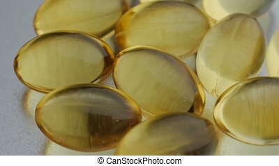 Fish oil capsules, rotation, macro, close up. - Omega 3 gold...