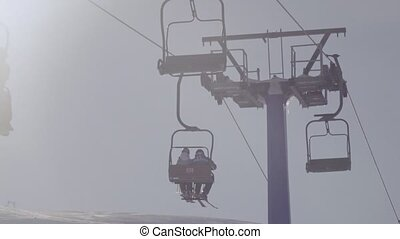 Silhouette of people on ski lift - In backlit sun operates...