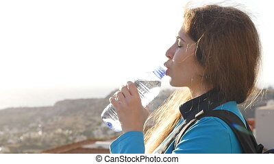 Woman tourist with backpack drinking water - Woman tourist...