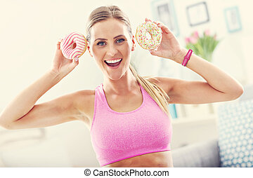 Sporty woman with donuts after workout