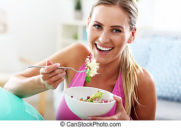 Young woman eating healthy salad after workout - Fit woman...