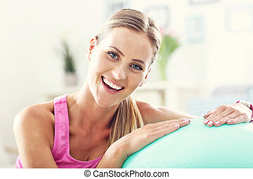 Smiling young woman with sports equipment at home.