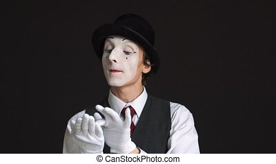 man MIME talking on an imaginary mobile phone over black...