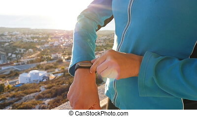 Fitness woman looking at smartwatch outdoor