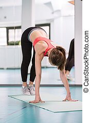 Young woman doing pilates exercises on the floor at the gym