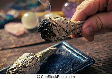 Man burning white sage incense - Man's hand with burning...