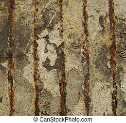 rusty metal embedded in a worn dirty concrete wall...