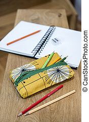 Pencil Case, Pencils, Notebook and Sharpener on Wooden Plank