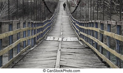Man is walking along on a rope suspension bridge.