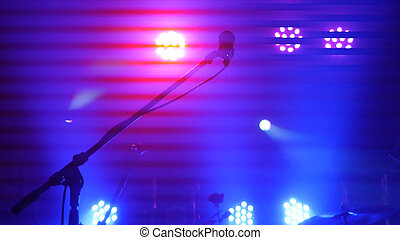 Stage lighting, equipment, beam and microphone stand in a...