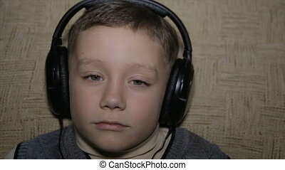 The boy listens to music through headphones