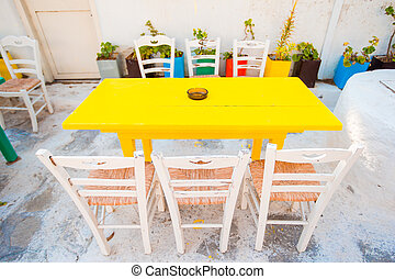 Empty openair cafe with colorful tables at greek old village...