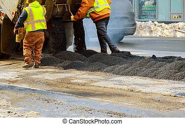Men hard working asphalting road with shovels - Men hard...