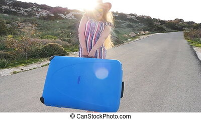 Happy Woman walking with suitcase on road, travel concept