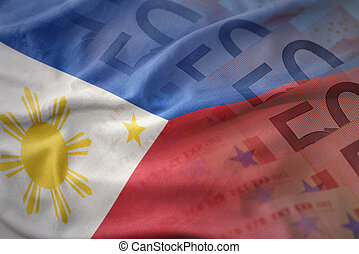 colorful waving national flag of philippines on a euro money banknotes background. finance concept