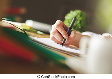 Girl sketching in notepad - Side view of girl's hand...