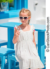 Little girl eating ice-cream outdoors at summer in outdoor...