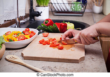 Child hands slicing cherry tomatos for a fresh vegetables salad