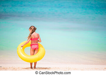 Little girl with yellow inflatable rubber circle going to...