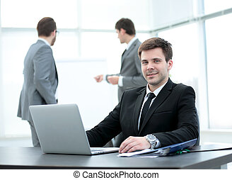successful businessman sitting at the table with an open...