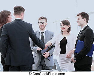 business partners shake hands before signing the contract in...