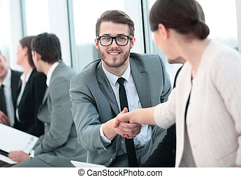 closeup of the employee welcomes colleague with a handshake...