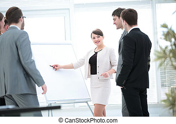 copywriter and designers stand next to a blank poster and...